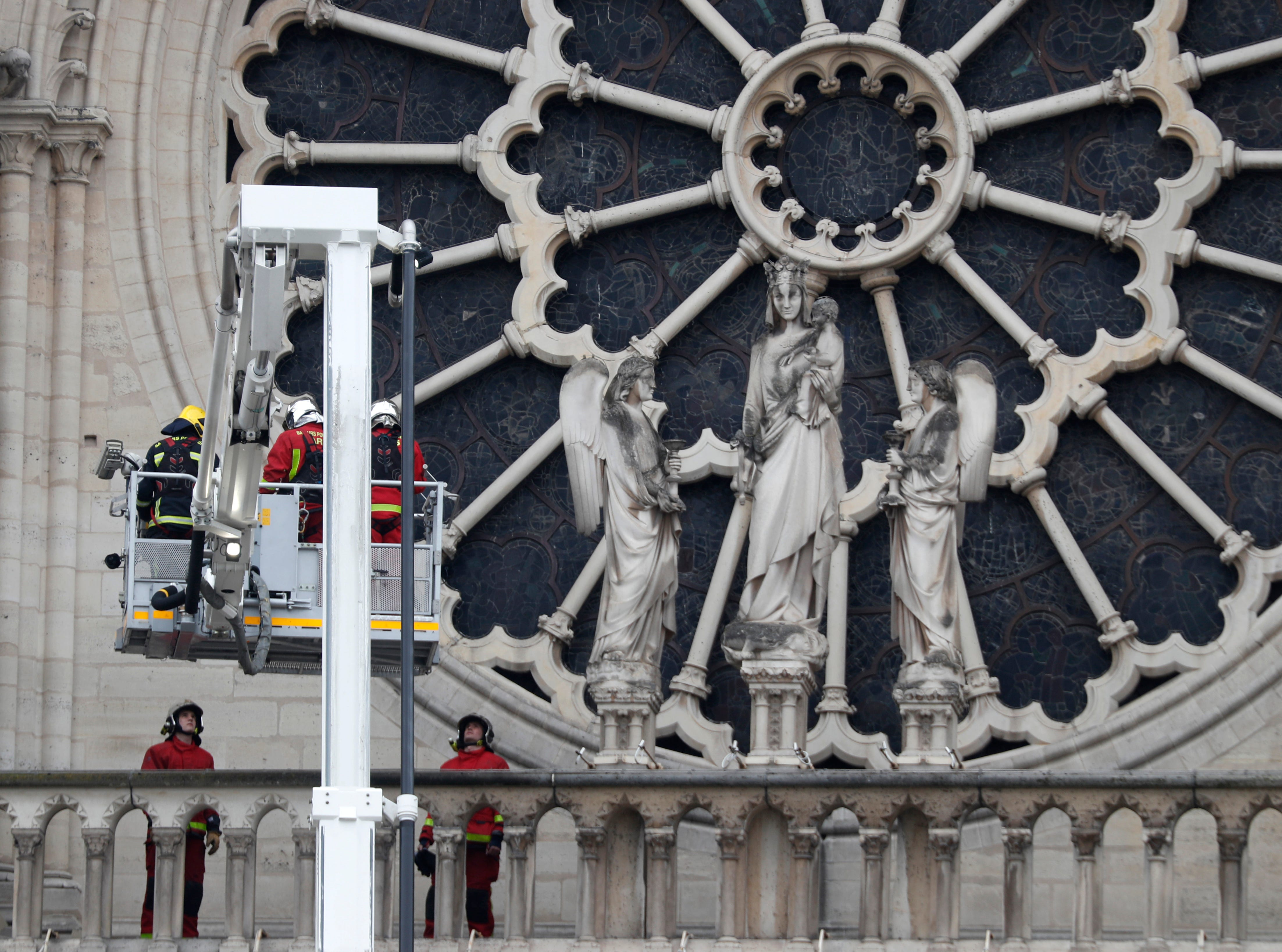 Firefighters work near the rose window of Notre Dame cathedral Tuesday April 16, 2019 in Paris. Experts assessed the blackened shell of Paris' iconic Notre Dame Tuesday morning to establish next steps to save what remains after a devastating fire destroyed much of the cathedral that had survived almost 900 years of history. (AP Photo/Thibault Camus)