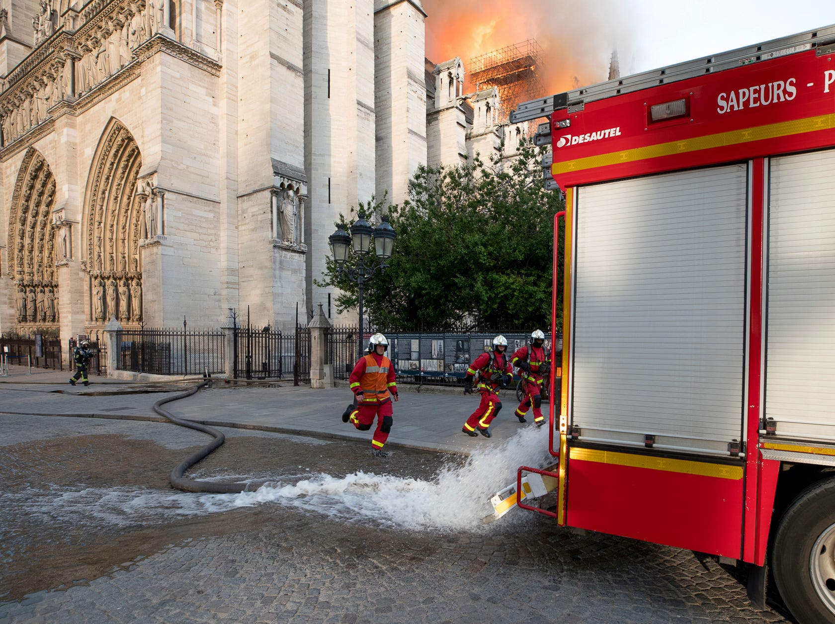 This photo provided Tuesday April 16, 2019 by the Paris Fire Brigade shows fire fighters running near the burning Notre Dame cathedral, Monday April 15, 2019. Experts assessed the blackened shell of Paris' iconic Notre Dame Tuesday morning to establish next steps to save what remains after a devastating fire destroyed much of the cathedral that had survived almost 900 years of history. (Benoit Moser, BSPP via AP)
