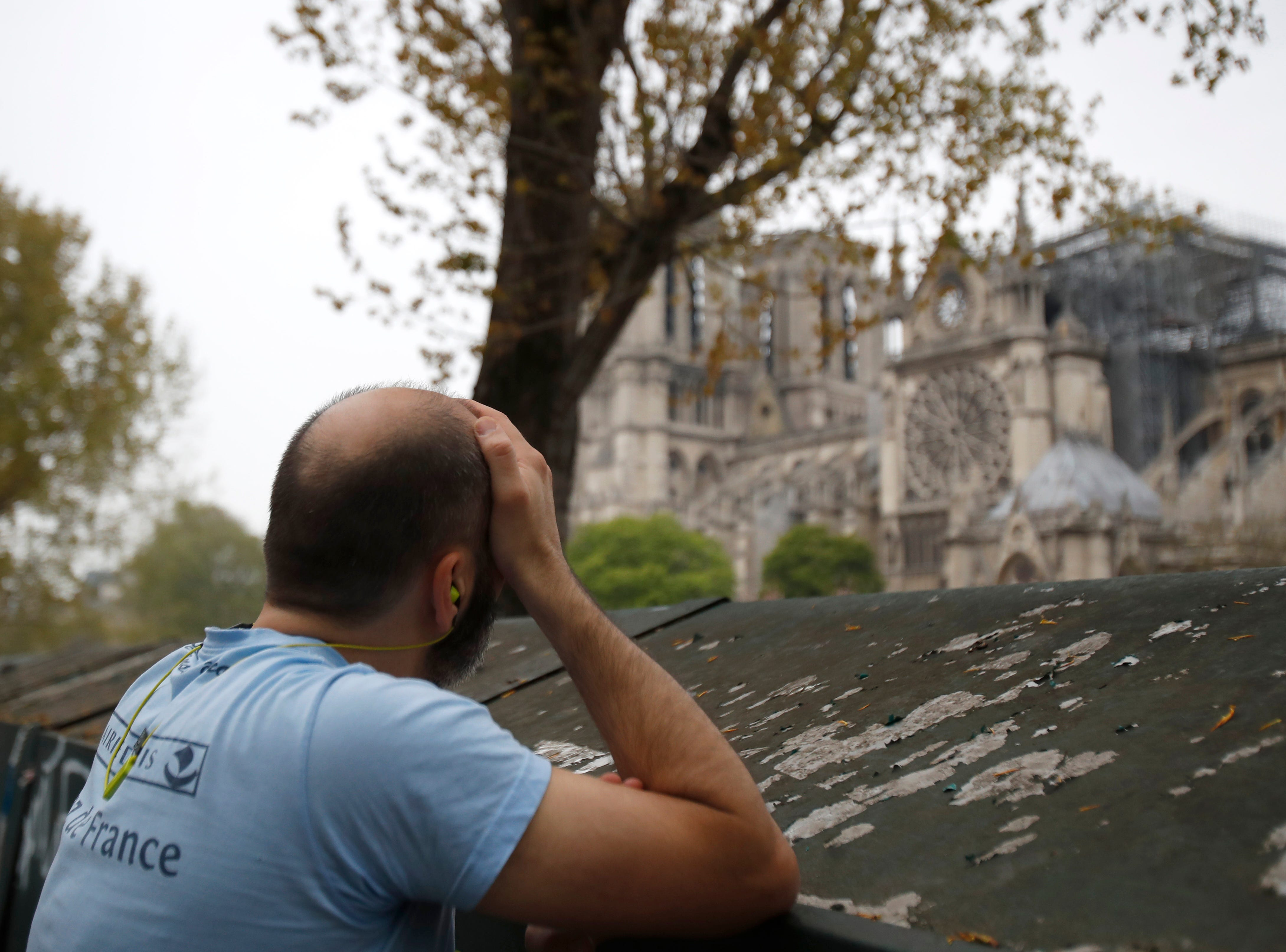 Man holds his head while watching the Notre Dame cathedral after the fire in Paris, Tuesday, April 16, 2019. Experts are assessing the blackened shell of Paris' iconic Notre Dame cathedral to establish next steps to save what remains after a devastating fire destroyed much of the almost 900-year-old building. With the fire that broke out Monday evening and quickly consumed the cathedral now under control, attention is turning to ensuring the structural integrity of the remaining building. (AP Photo/Christophe Ena)