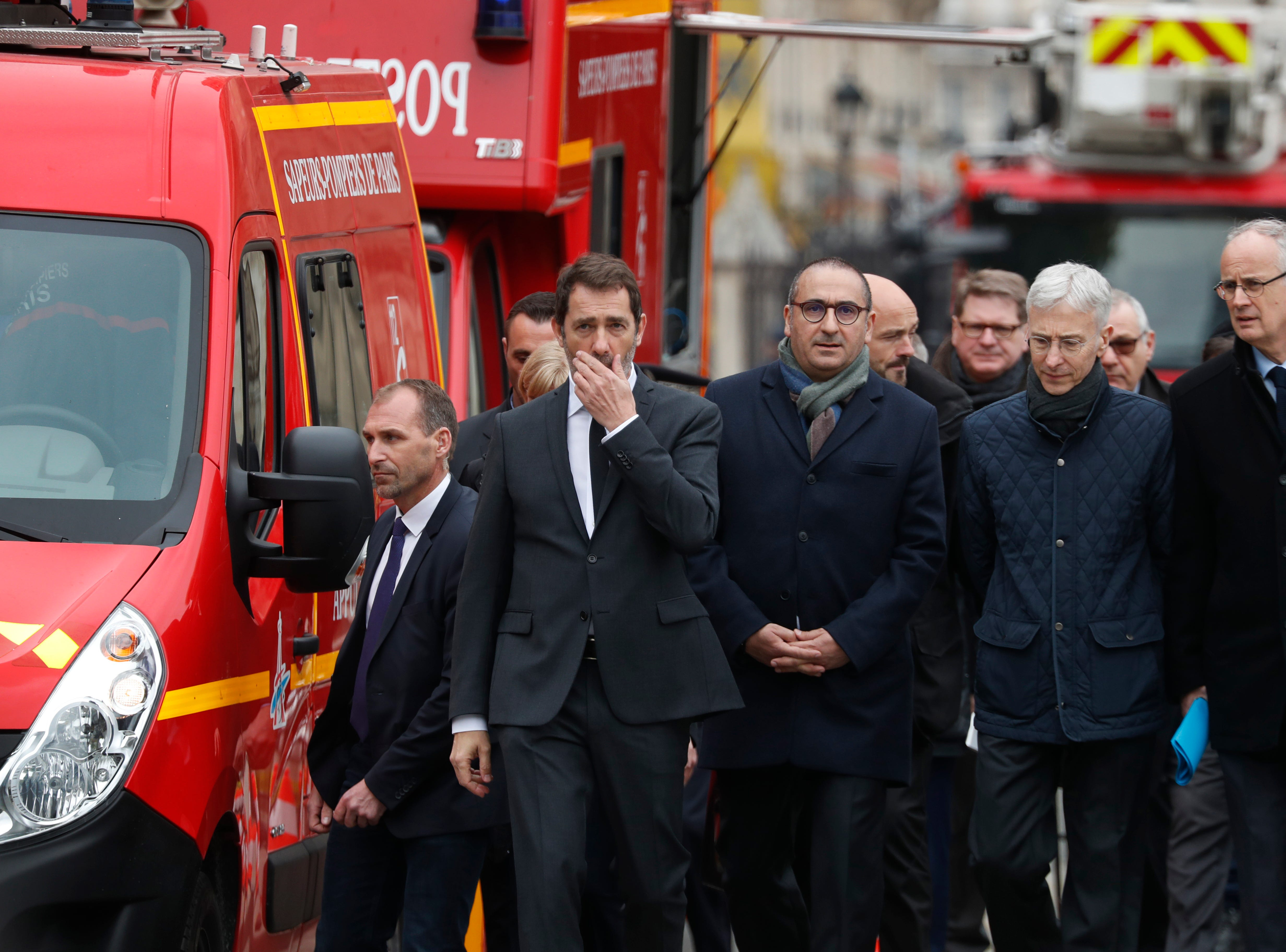 French Interior Minister Christophe Castaner, second left, and deputy Interior Minister Laurent Nunez, center, arrive at the damaged Notre Dame cathedral after the fire in Paris, Tuesday, April 16, 2019. Experts are assessing the blackened shell of Paris' iconic Notre Dame cathedral to establish next steps to save what remains after a devastating fire destroyed much of the almost 900-year-old building. With the fire that broke out Monday evening and quickly consumed the cathedral now under control, attention is turning to ensuring the structural integrity of the remaining building. (AP Photo/Thibault Camus)