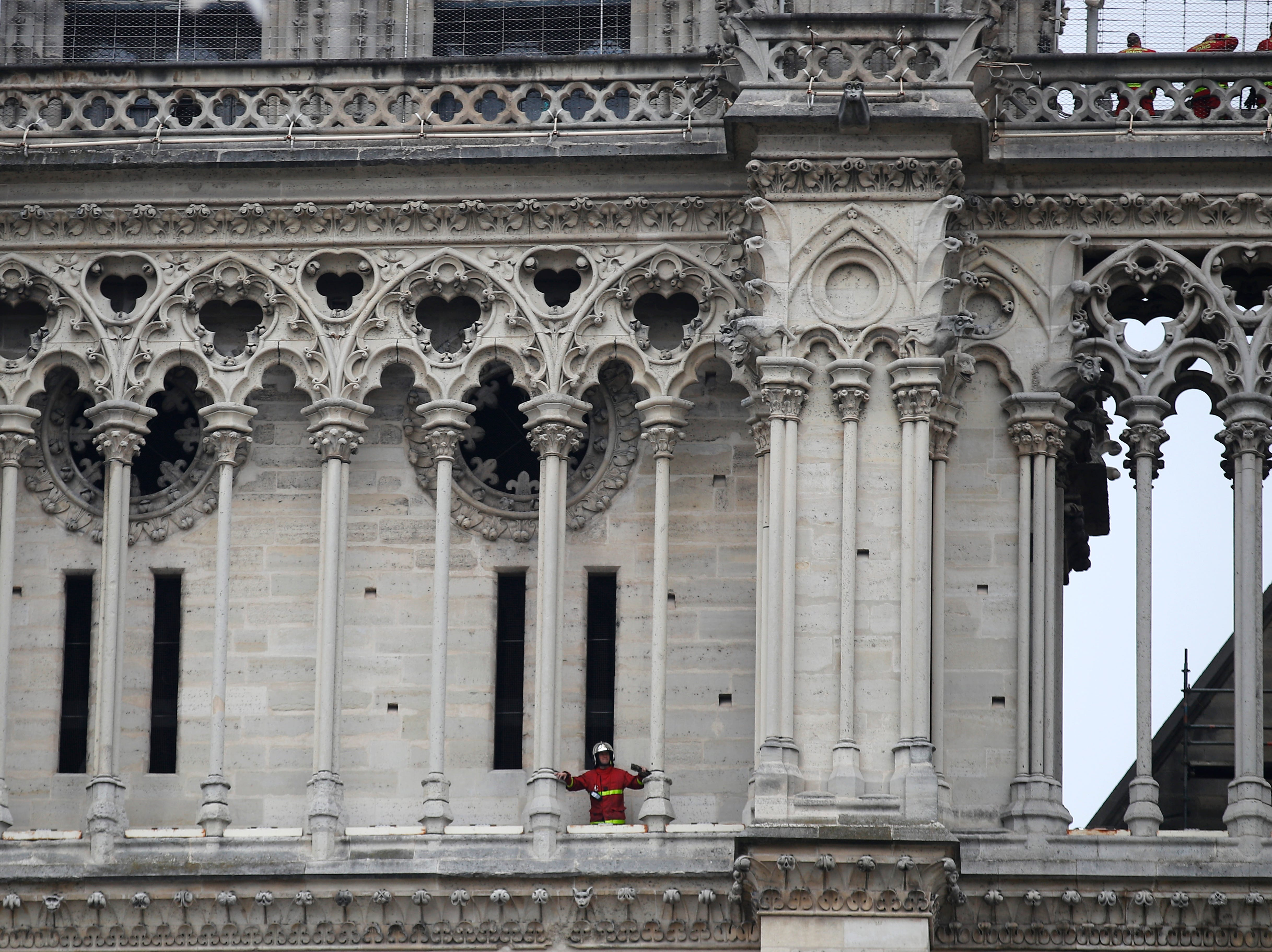 A firefighter is pictured at Notre Dame cathedral Tuesday April 16, 2019 in Paris. Firefighters declared success Tuesday in a more than 12-hour battle to extinguish an inferno engulfing Paris' iconic Notre Dame cathedral that claimed its spire and roof, but spared its bell towers. (AP Photo/Francois Mori)