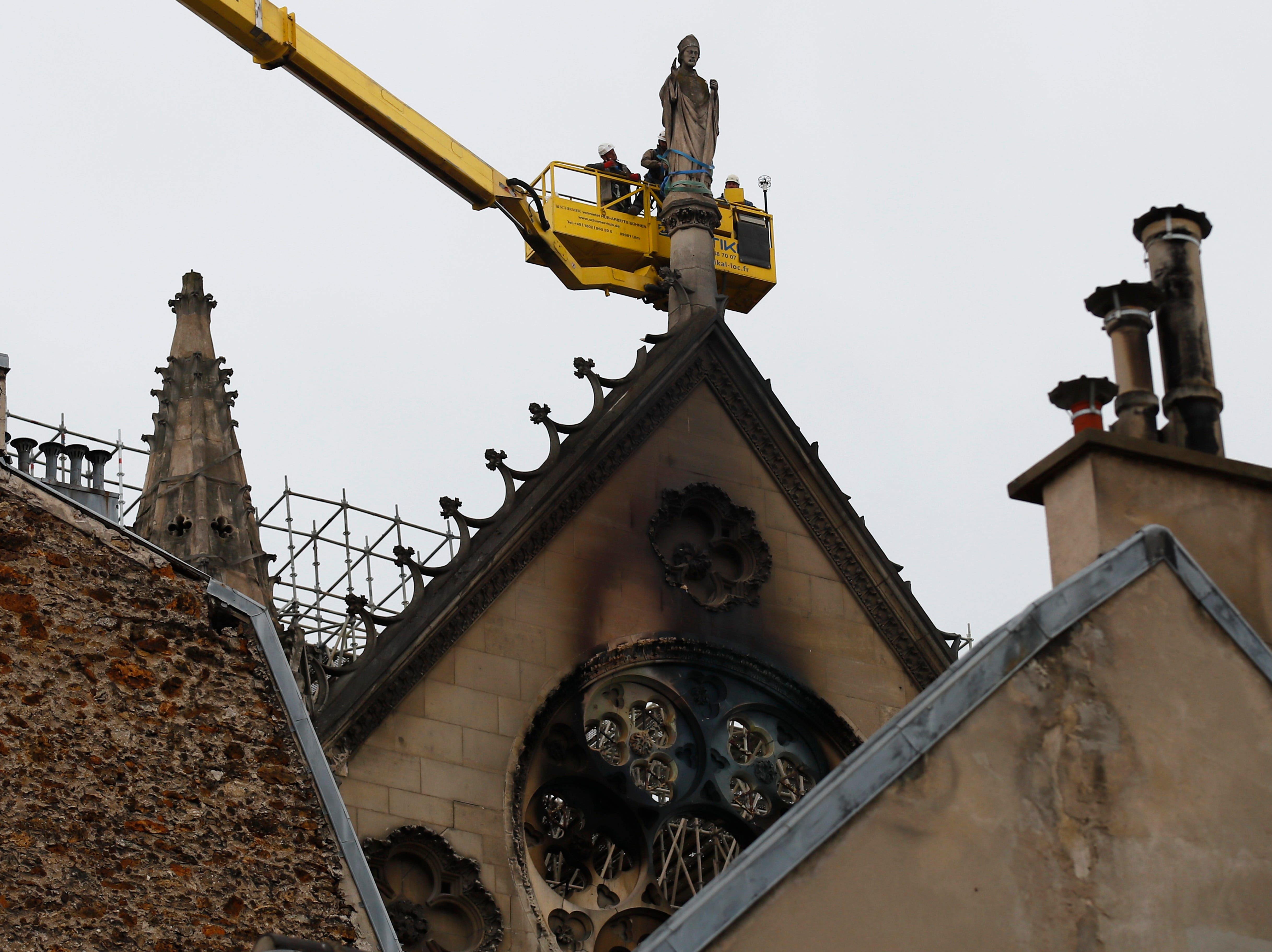 Workers atop a crane fix a statue at Notre Dame cathedral Tuesday April 16, 2019 in Paris. Firefighters declared success Tuesday in a more than 12-hour battle to extinguish an inferno engulfing Paris' iconic Notre Dame cathedral that claimed its spire and roof, but spared its bell towers. (AP Photo/Francois Mori)