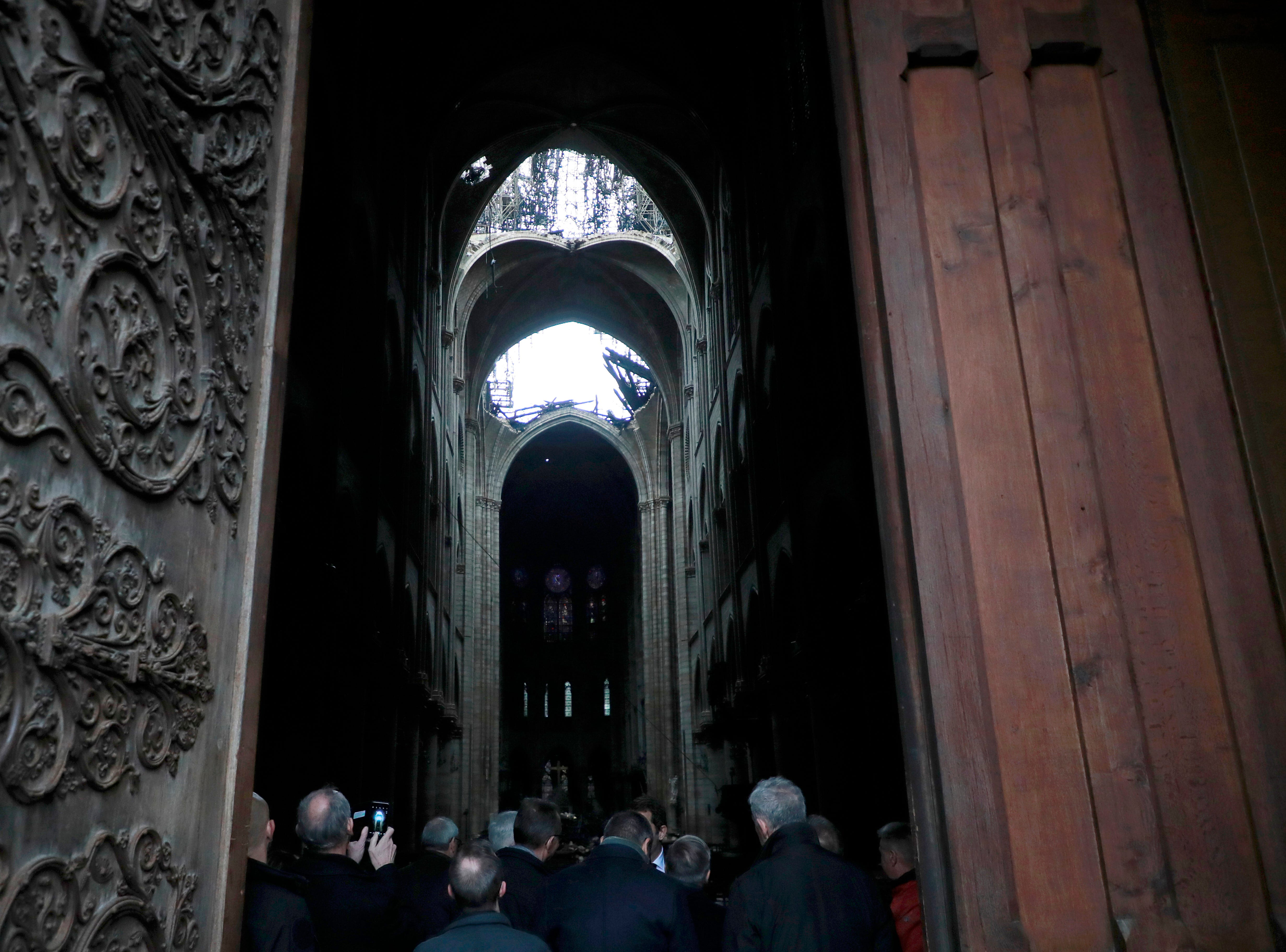 A hole is seen in the dome inside Notre cathedral in Paris, Tuesday, April 16, 2019. Firefighters declared success Tuesday in a more than 12-hour battle to extinguish an inferno engulfing Paris' iconic Notre Dame cathedral that claimed its spire and roof, but spared its bell towers and the purported Crown of Christ. (Christophe Petit Tesson, Pool via AP)