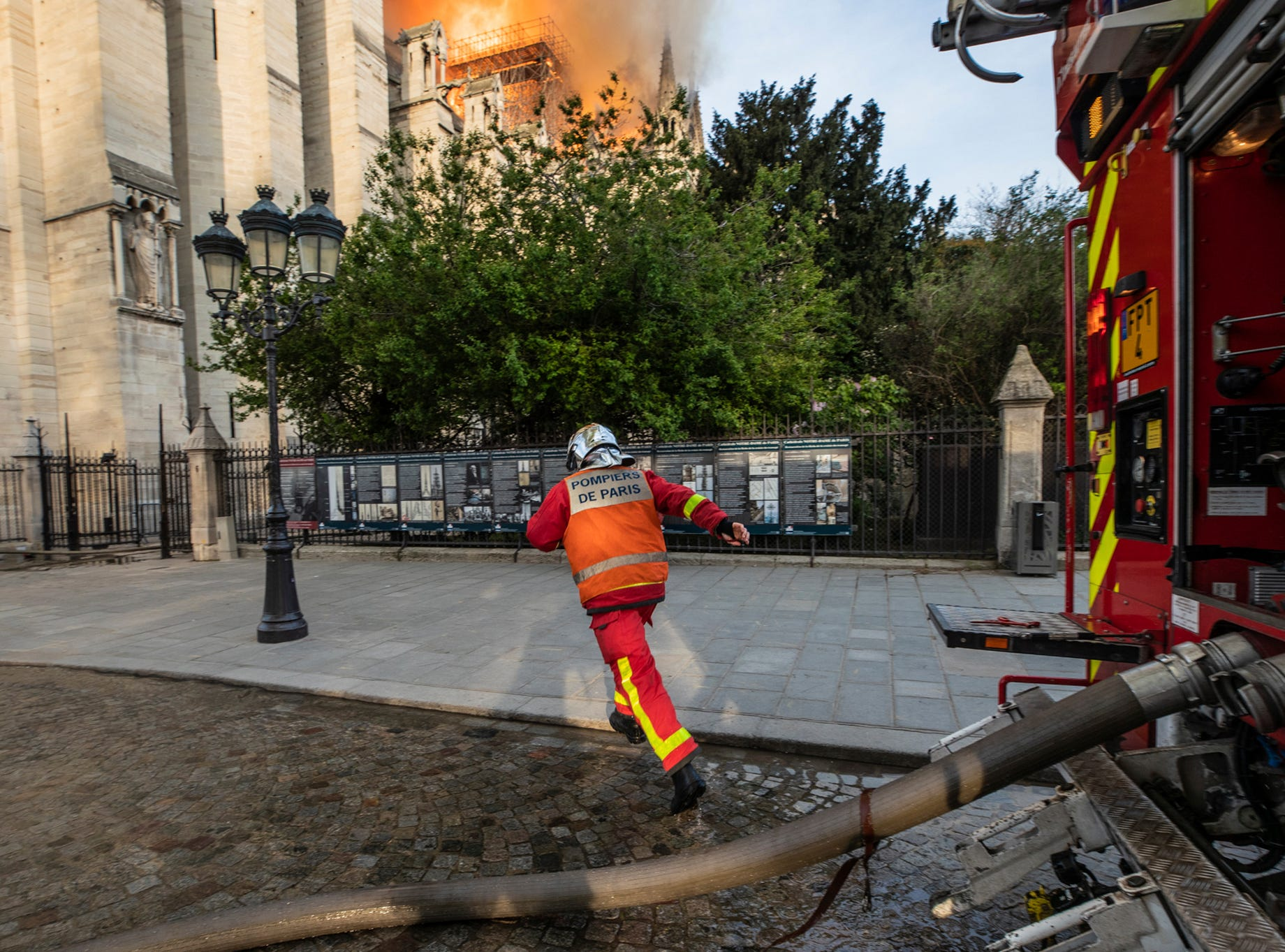 This photo provided Tuesday April 16, 2019 by the Paris Fire Brigade shows a fire fighter rushing at the burning Notre Dame cathedral, Monday April 15, 2019. Experts assessed the blackened shell of Paris' iconic Notre Dame Tuesday morning to establish next steps to save what remains after a devastating fire destroyed much of the cathedral that had survived almost 900 years of history. (Benoit Moser, BSPP via AP)