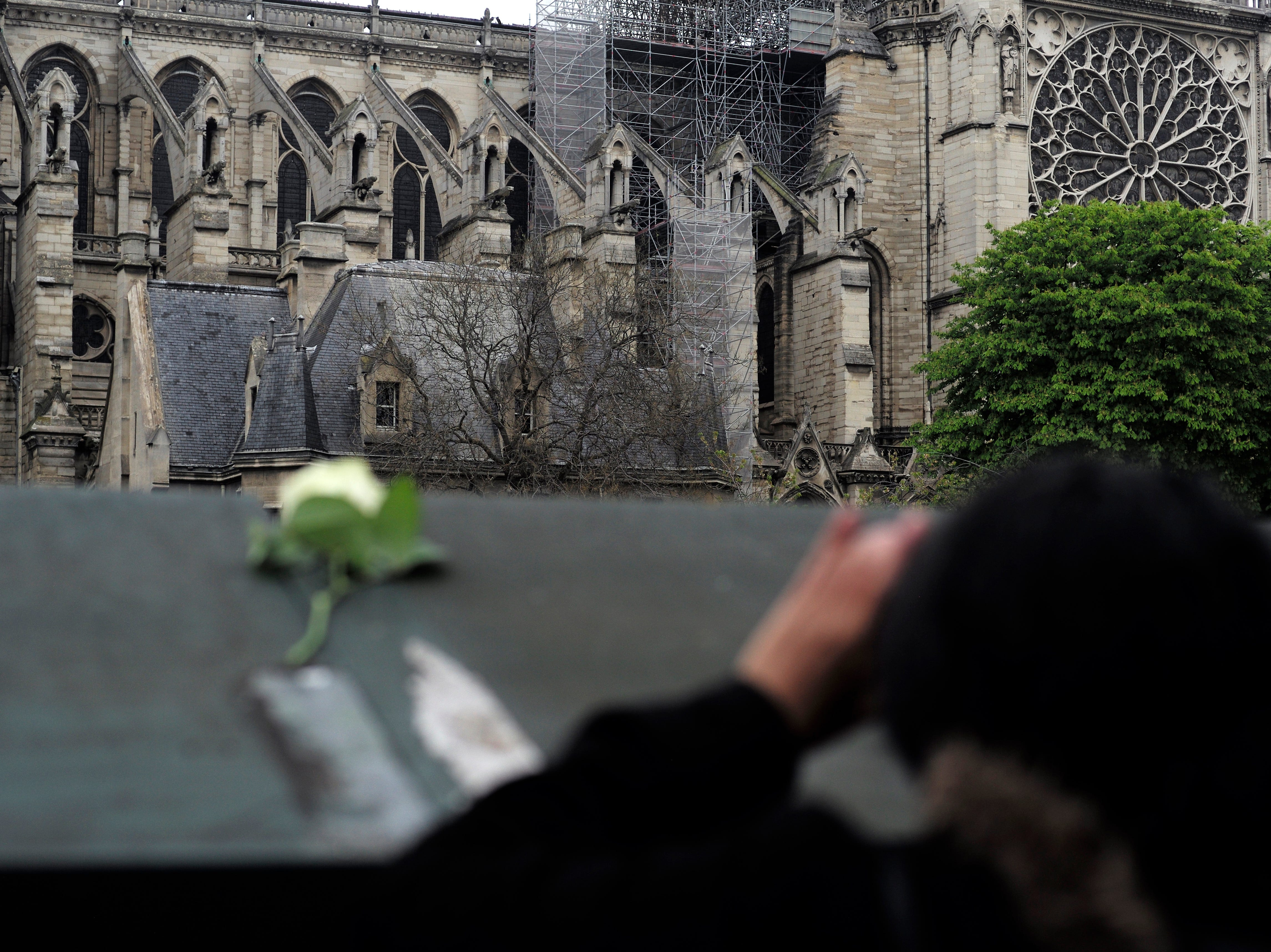 A woman photographs the Notre Dame cathedral after the fire in Paris, Tuesday, April 16, 2019. Experts are assessing the blackened shell of Paris' iconic Notre Dame cathedral to establish next steps to save what remains after a devastating fire destroyed much of the almost 900-year-old building. With the fire that broke out Monday evening and quickly consumed the cathedral now under control, attention is turning to ensuring the structural integrity of the remaining building. (AP Photo/Kamil Zihnioglu)