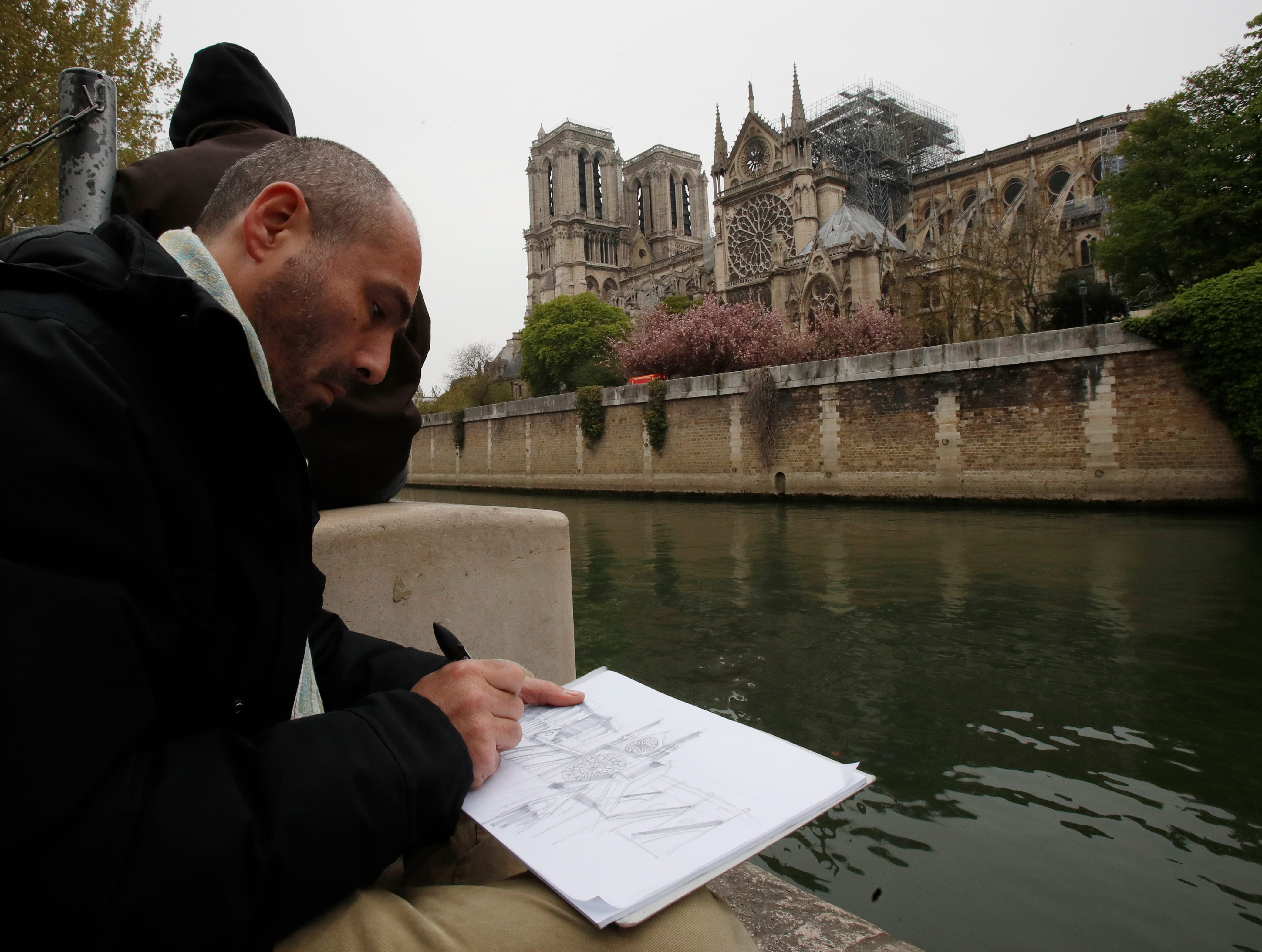 Man makes a drawing of the Notre Dame cathedral after the fire in Paris, Tuesday, April 16, 2019. Experts are assessing the blackened shell of Paris' iconic Notre Dame cathedral to establish next steps to save what remains after a devastating fire destroyed much of the almost 900-year-old building. With the fire that broke out Monday evening and quickly consumed the cathedral now under control, attention is turning to ensuring the structural integrity of the remaining building. (AP Photo/Christophe Ena)