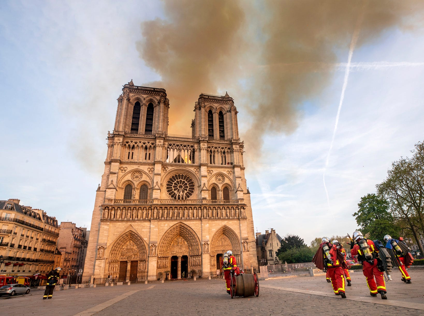 This photo provided Tuesday April 16, 2019 by the Paris Fire Brigade shows fire fighters heading to the burning Notre Dame cathedral, Monday April 15, 2019. Experts assessed the blackened shell of Paris' iconic Notre Dame Tuesday morning to establish next steps to save what remains after a devastating fire destroyed much of the cathedral that had survived almost 900 years of history. (Benoit Moser/BSPP via AP)