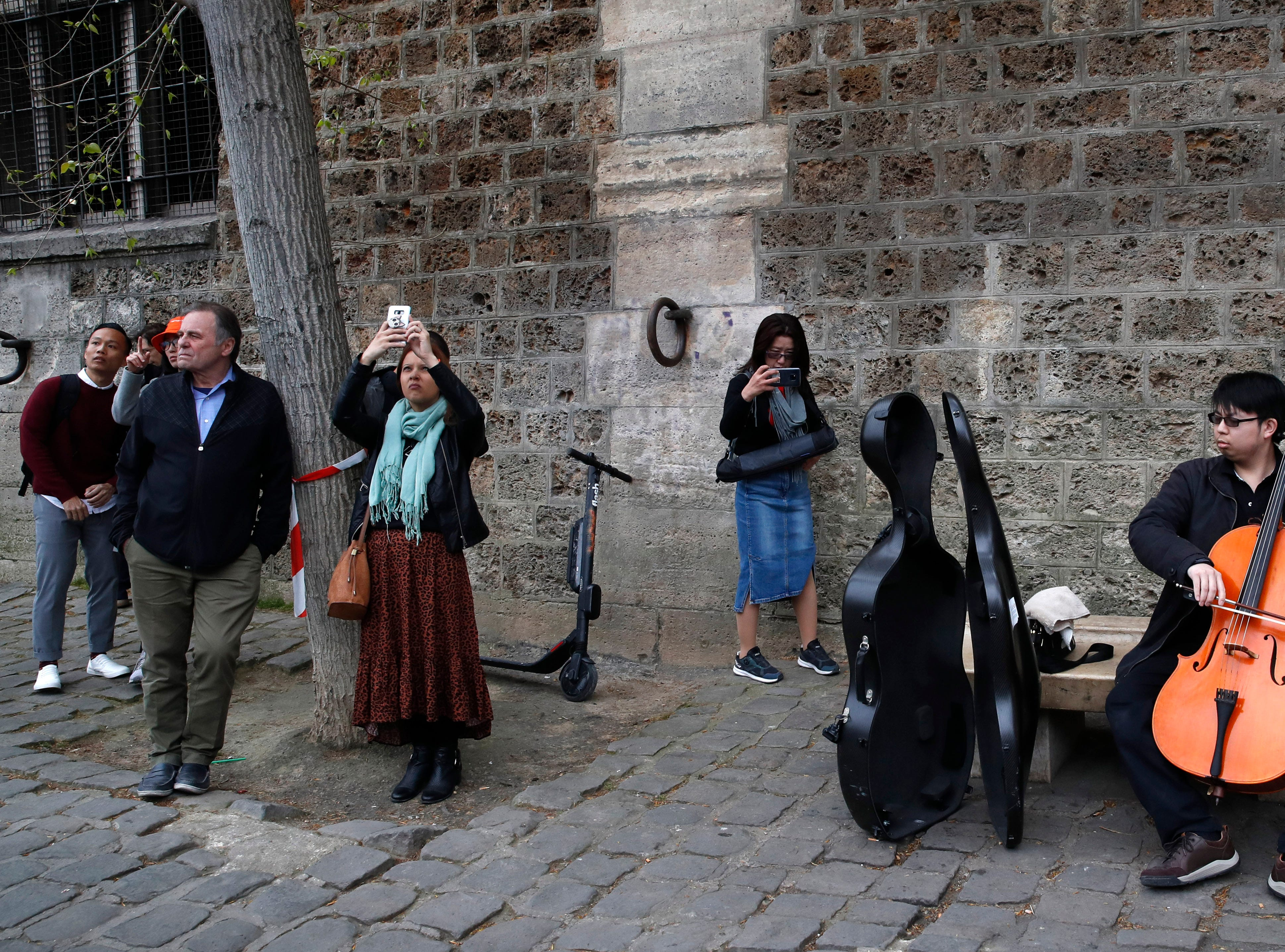 Man plays violoncello as people came to watch and photograph the Notre Dame cathedral after the fire in Paris, Tuesday, April 16, 2019. Experts are assessing the blackened shell of Paris' iconic Notre Dame cathedral to establish next steps to save what remains after a devastating fire destroyed much of the almost 900-year-old building. With the fire that broke out Monday evening and quickly consumed the cathedral now under control, attention is turning to ensuring the structural integrity of the remaining building. (AP Photo/Christophe Ena)