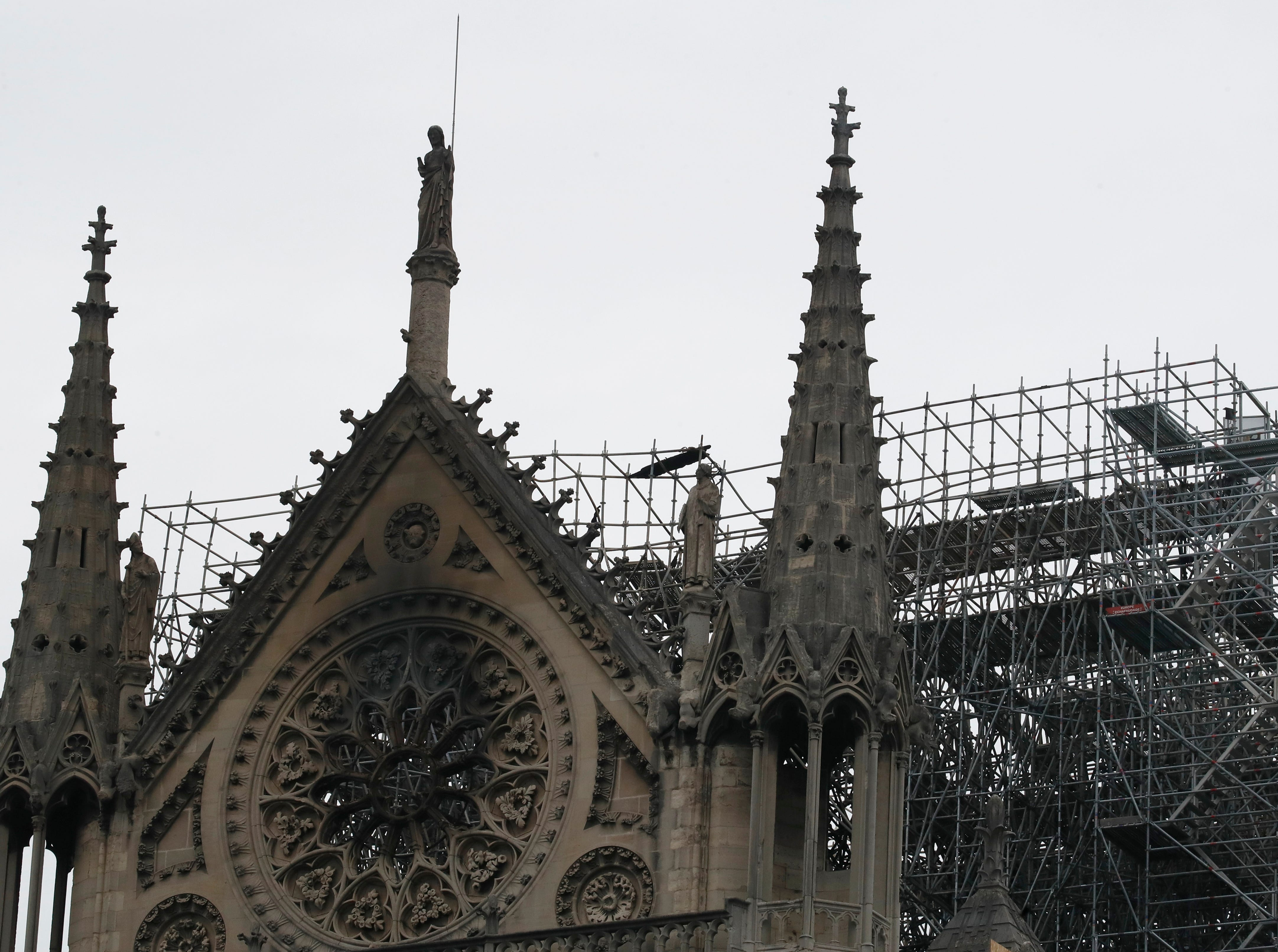 View of the Notre Dame cathedral after the fire in Paris, Tuesday, April 16, 2019. Experts are assessing the blackened shell of Paris' iconic Notre Dame cathedral to establish next steps to save what remains after a devastating fire destroyed much of the almost 900-year-old building. With the fire that broke out Monday evening and quickly consumed the cathedral now under control, attention is turning to ensuring the structural integrity of the remaining building. (AP Photo/Christophe Ena)
