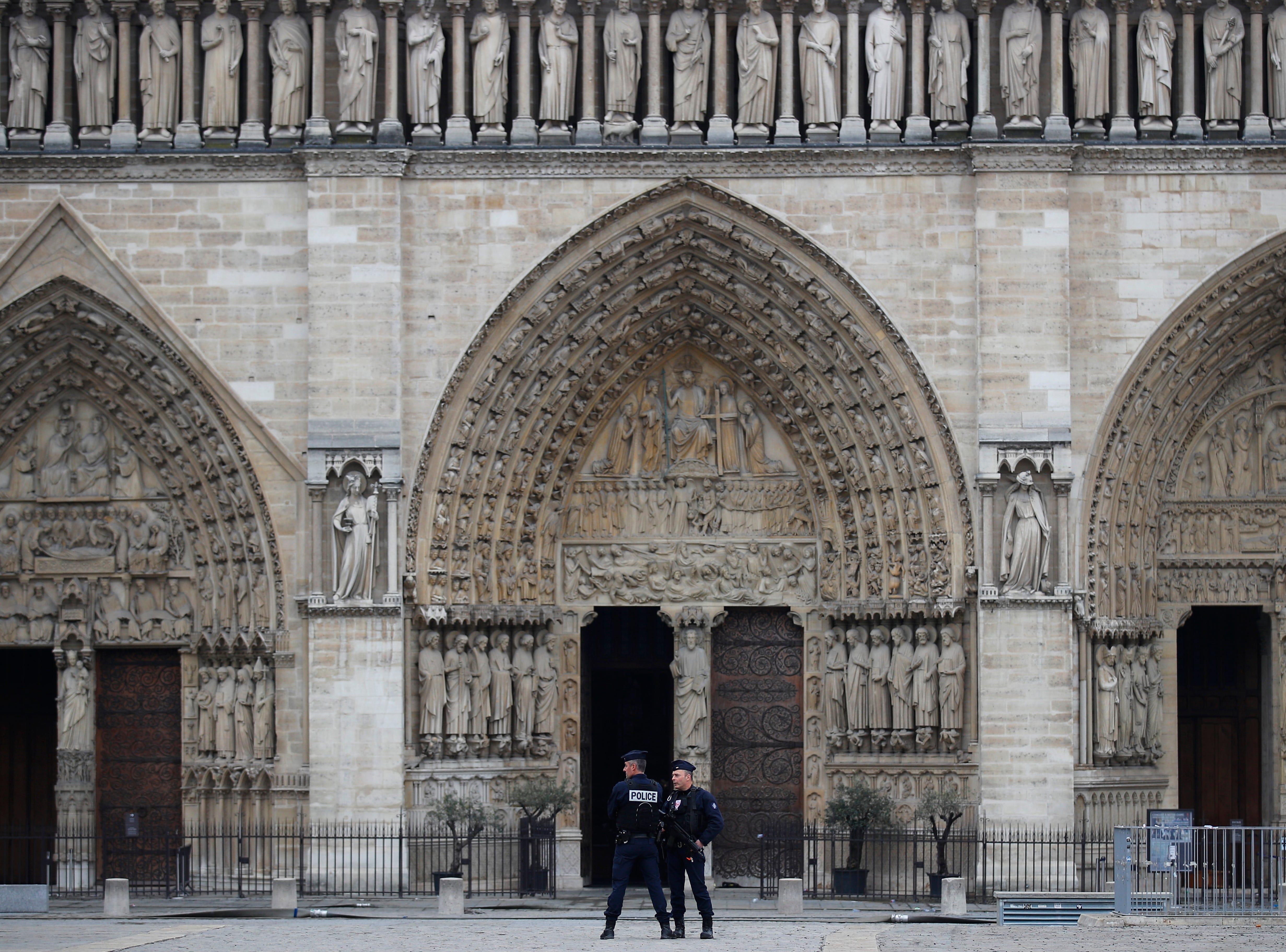 Police officers patrol outside Notre Dame cathedral Tuesday April 16, 2019 in Paris. Firefighters declared success Tuesday in a more than 12-hour battle to extinguish an inferno engulfing Paris' iconic Notre Dame cathedral that claimed its spire and roof, but spared its bell towers. (AP Photo/Francois Mori)
