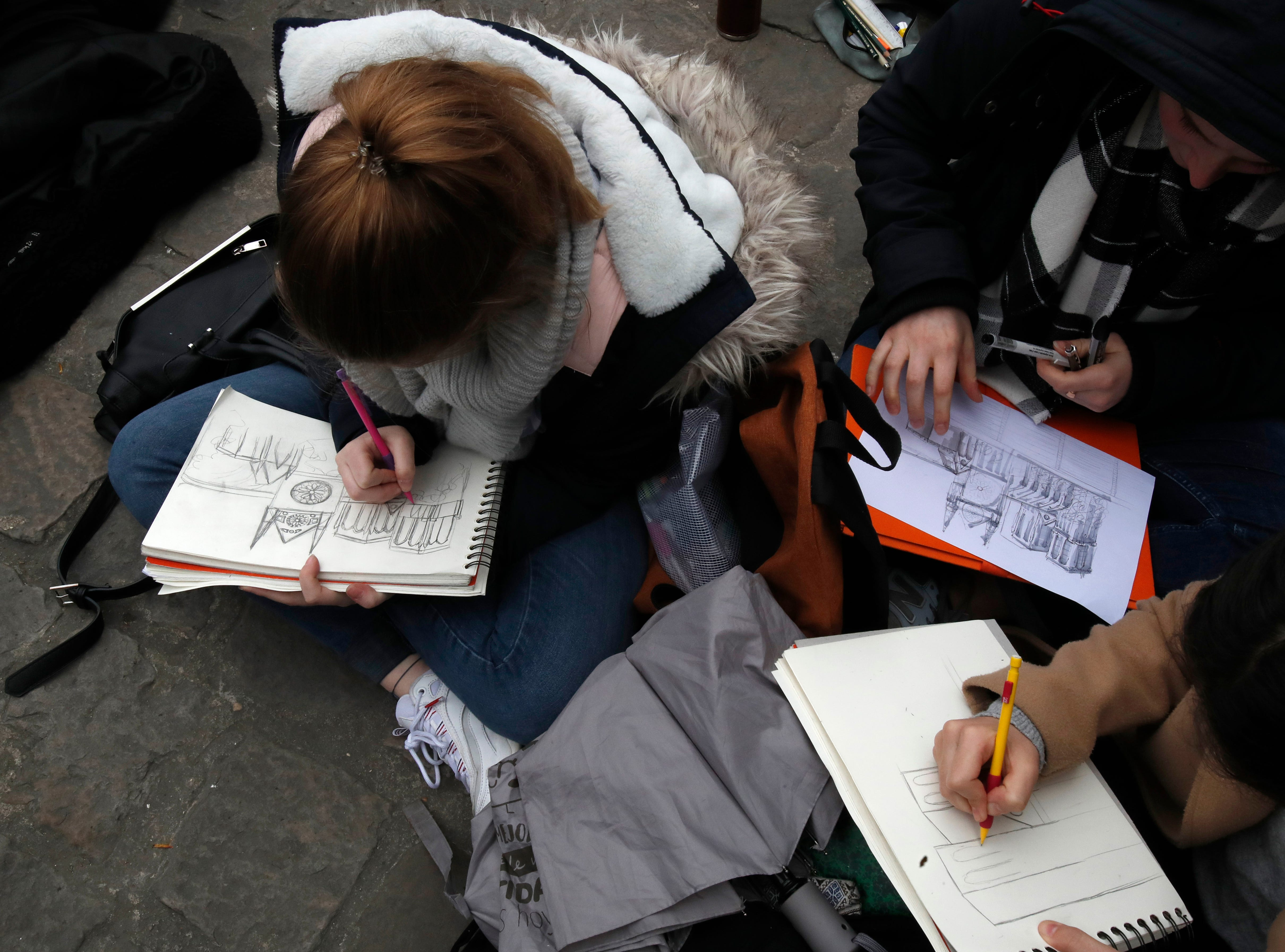 People make drawings of the Notre Dame cathedral after the fire in Paris, Tuesday, April 16, 2019. Experts are assessing the blackened shell of Paris' iconic Notre Dame cathedral to establish next steps to save what remains after a devastating fire destroyed much of the almost 900-year-old building. With the fire that broke out Monday evening and quickly consumed the cathedral now under control, attention is turning to ensuring the structural integrity of the remaining building. (AP Photo/Christophe Ena)