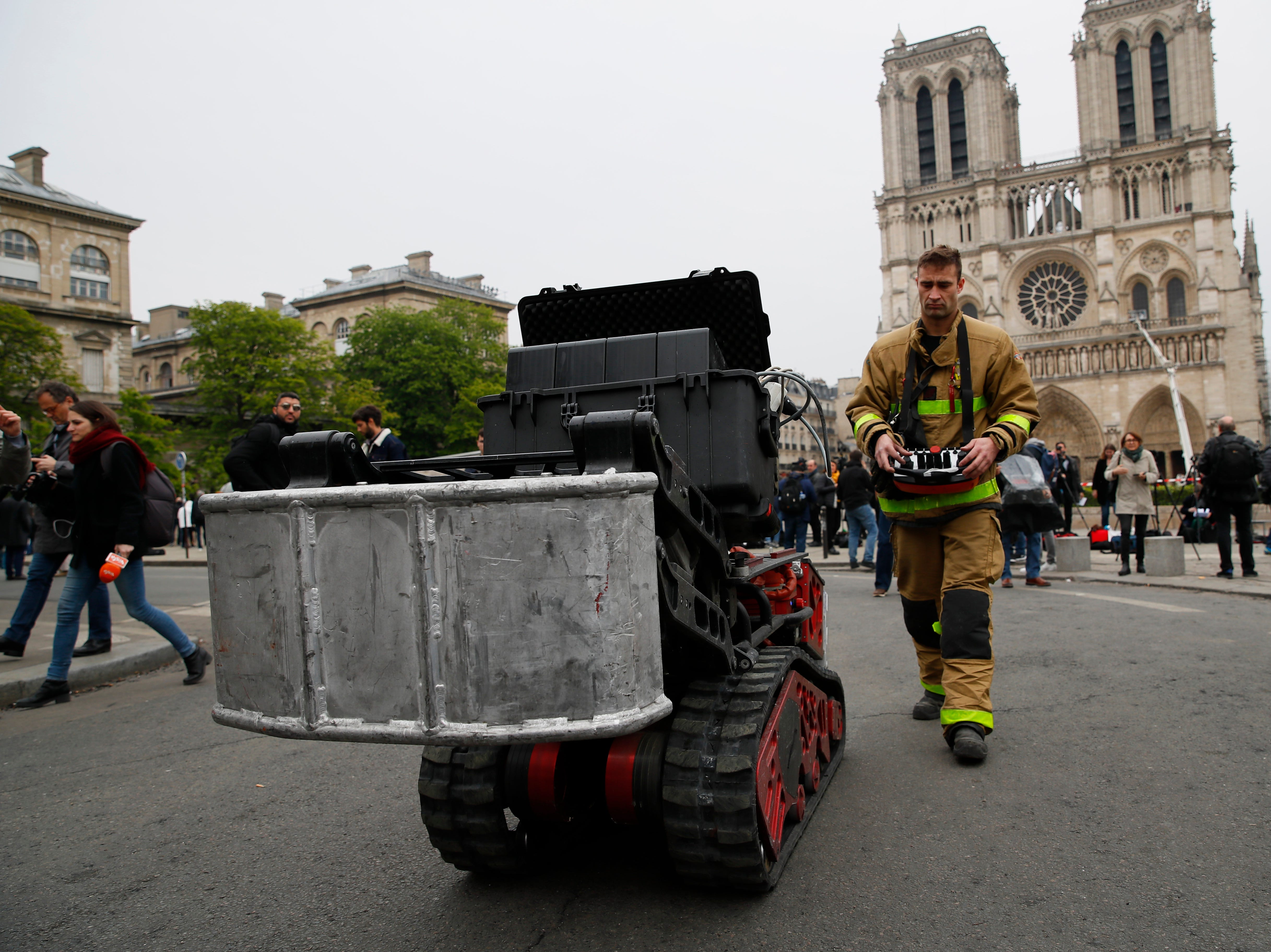 A firefighter operates a machine by remote control outside Notre Dame cathedral Tuesday April 16, 2019 in Paris. Experts assessed the blackened shell of Paris' iconic Notre Dame Tuesday morning to establish next steps to save what remains after a devastating fire destroyed much of the cathedral that had survived almost 900 years of history. (AP Photo/Francois Mori)