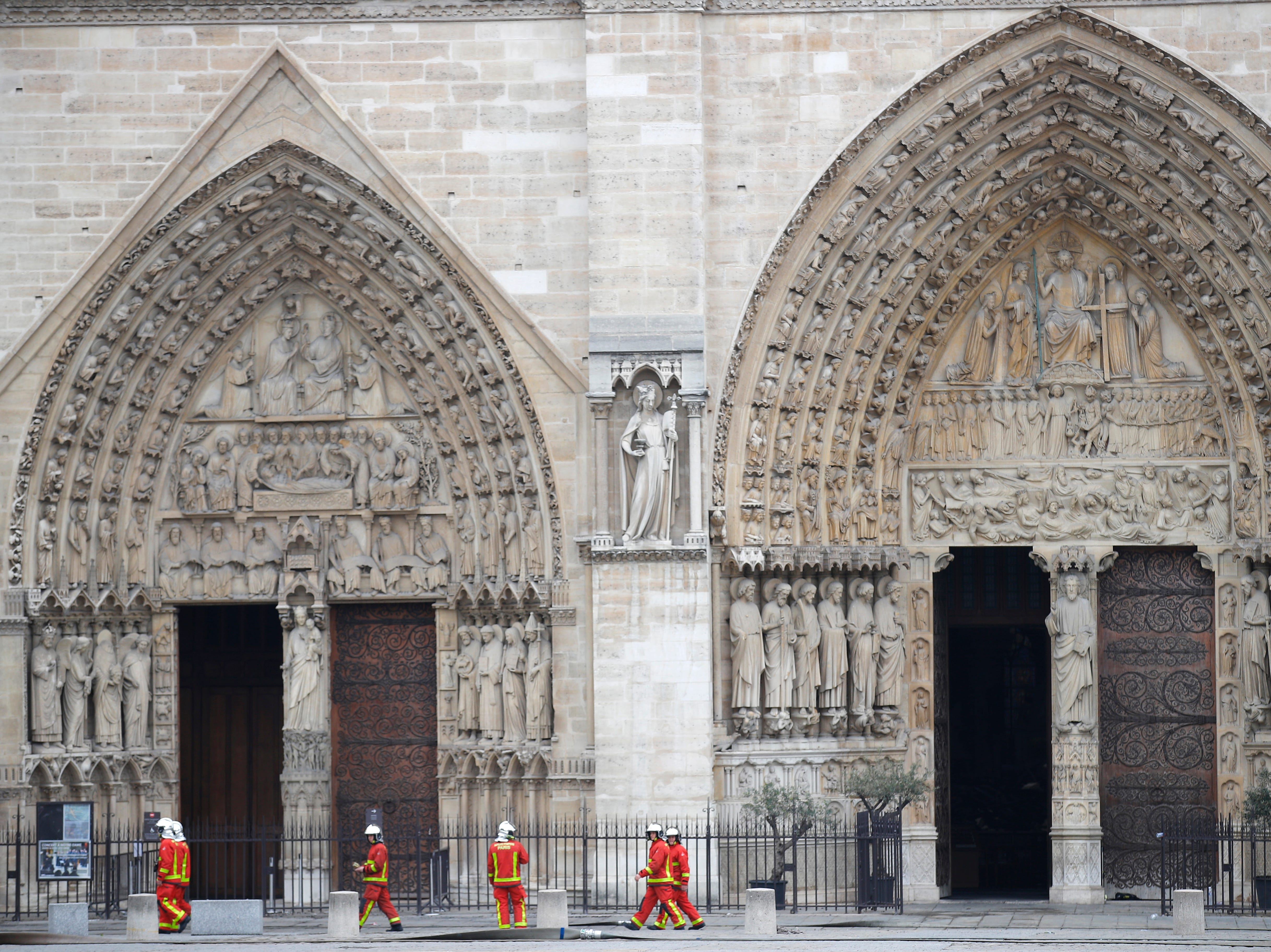 Firefighters walk outside the main entrances of Notre Dame cathedral Tuesday April 16, 2019 in Paris. Firefighters declared success Tuesday in a more than 12-hour battle to extinguish an inferno engulfing Paris' iconic Notre Dame cathedral that claimed its spire and roof, but spared its bell towers. (AP Photo/Francois Mori)