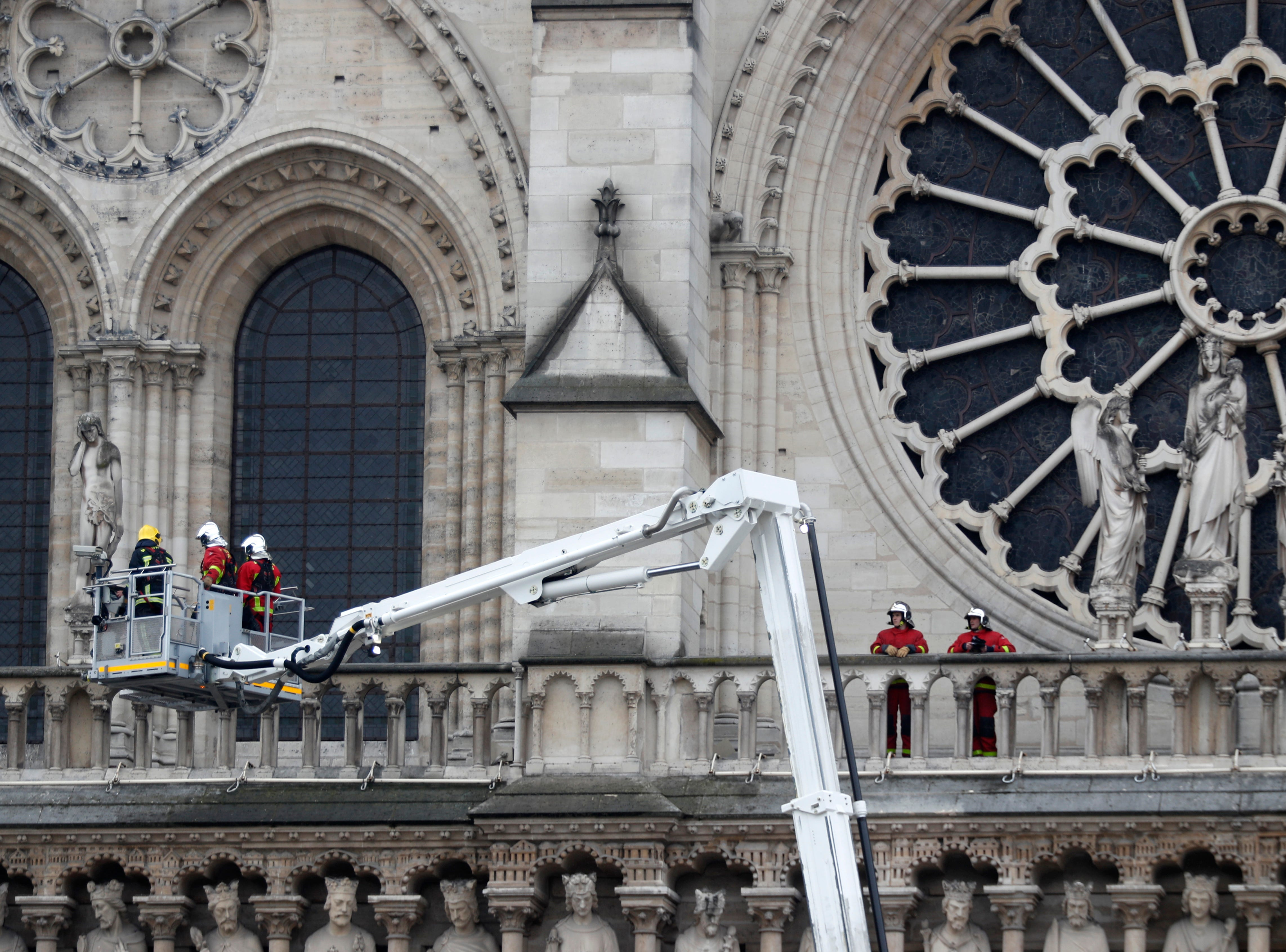 Firefighters work at the facade of Notre Dame cathedral Tuesday April 16, 2019 in Paris. Experts assessed the blackened shell of Paris' iconic Notre Dame Tuesday morning to establish next steps to save what remains after a devastating fire destroyed much of the cathedral that had survived almost 900 years of history. (AP Photo/Thibault Camus)