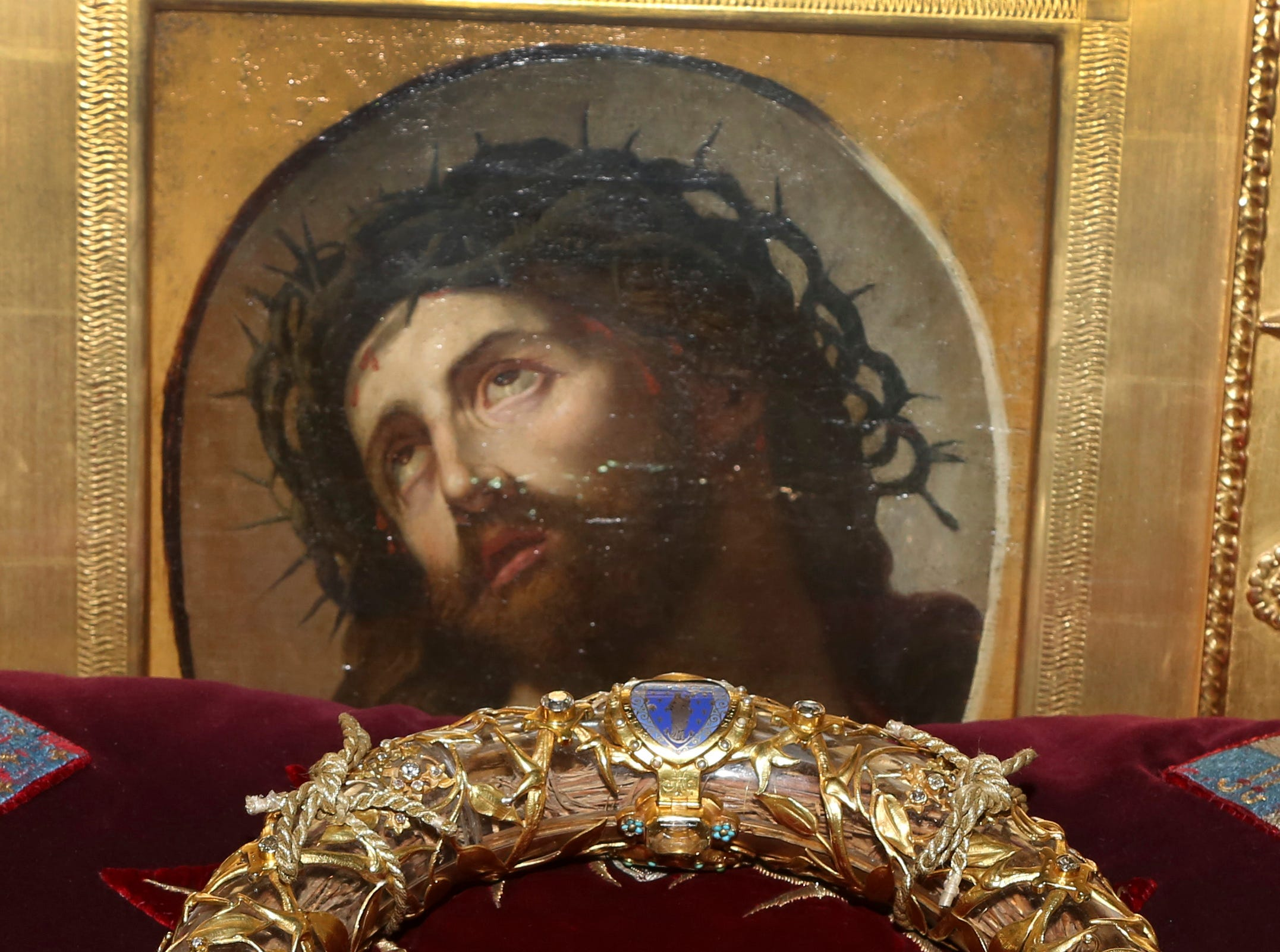 """FILE - In this Friday March 21, 2014 file photo a crown of thorns which was believed to have been worn by Jesus Christ and which was bought by King Louis IX in 1239 is presented at Notre Dame Cathedral in Paris. Paris' mayor, Anne Hidalgo, said a significant collection of art and holy objects inside the church had been recovered from the fire at Notre Dame cathedral. In a tweet later, she thanked firefighters and others who formed a human chain to save artifacts. """"The crown of thorns, the tunic of St. Louis and many other major artifacts are now in a safe place,"""" she wrote. (AP Photo/Remy de la Mauviniere, File)"""