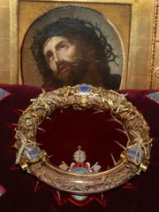 "FILE - In this Friday March 21, 2014 file photo a crown of thorns which was believed to have been worn by Jesus Christ and which was bought by King Louis IX in 1239 is presented at Notre Dame Cathedral in Paris. Paris' mayor, Anne Hidalgo, said a significant collection of art and holy objects inside the church had been recovered from the fire at Notre Dame cathedral. In a tweet later, she thanked firefighters and others who formed a human chain to save artifacts. ""The crown of thorns, the tunic of St. Louis and many other major artifacts are now in a safe place,"" she wrote. (AP Photo/Remy de la Mauviniere, File)"