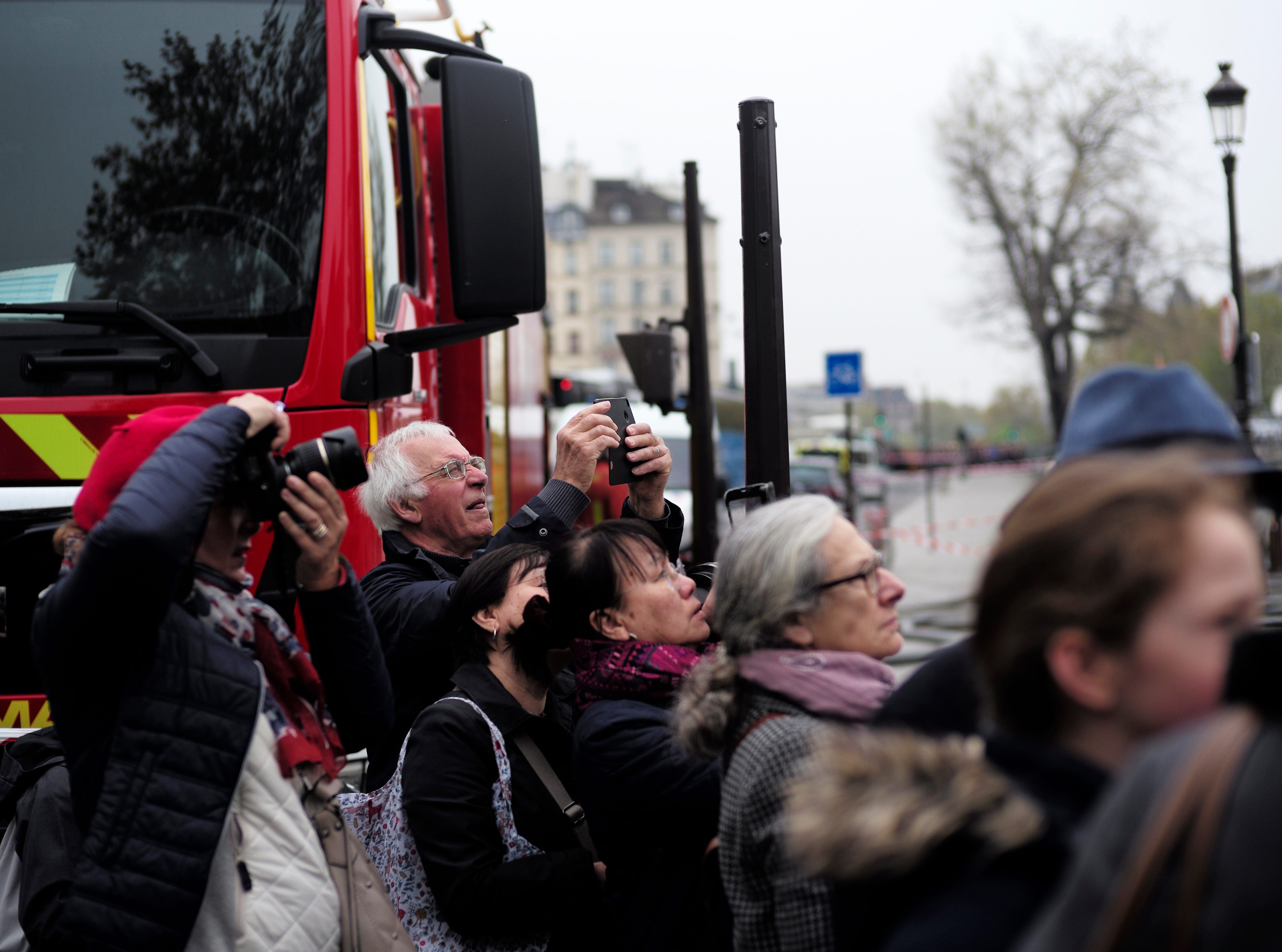 People watch and photograph the Notre Dame cathedral after the fire in Paris, Tuesday, April 16, 2019. Experts are assessing the blackened shell of Paris' iconic Notre Dame cathedral to establish next steps to save what remains after a devastating fire destroyed much of the almost 900-year-old building. With the fire that broke out Monday evening and quickly consumed the cathedral now under control, attention is turning to ensuring the structural integrity of the remaining building. (AP Photo/Kamil Zihnioglu)