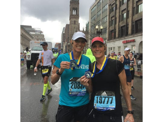Twin sisters Kim Ray, left, and Kris Harrison of Great Falls were all smiles after completing the Boston Marathon on Monday.