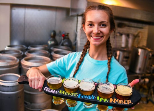 Server Lindsey Trepton paddles out five ponies of various types draught beer available at the Guam Brewery Tap House in Tumon on Thursday, April 11, 2019.
