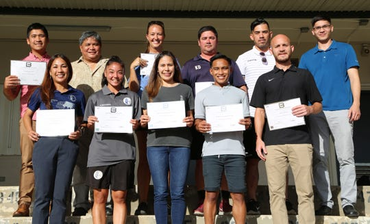 """Coaches who recently earned their AFC """"B"""" Coaching Certificates pose for a group photo after officially receiving their AFC certificates. The certificate course, facilitated by visiting instructor Yusuke Adachi and assistant instructor Kazunori Ohara, concluded Jan. 25. In the photo are, front from left, Rhoda Bamba, Kimberly Sherman, Anjelica Perez, Bryan Cadiz, and Jeremy Wendal. In the back row, from left, are Ross Awa, GFA President Tino San Gil, Maggie Phillips, Keith Dickson, GFA Coach Education Development Officer Dominic Gadia, and GFA General Secretary Micah Paulino. Not pictured: coaches Derrick Cruz, Matthew Elwell, Dr. Gary Larkin, and Chyna Ramirez. Also earning their AFC """"B"""" Coaching Certificates from the group are Jershwin Angeles and Lalaine Pagarao from the Northern Mariana Islands. NMI's Ruselle Zapanta received a pro-pass from Guam's 2018-2019 course."""