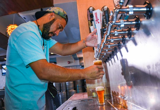 Bartender Cory Caso carefully pours out a pony of draught beer at the Guam Brewery Tap House in Tumon on Thursday, April 11, 2019.