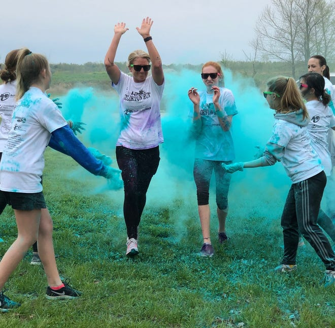 HNS mom Jamie Smith and HNS sixth-grade student Kate Cassidy dash through a cloud of blue powder at Sandy Lee Watkins Park during the school's Color Run.