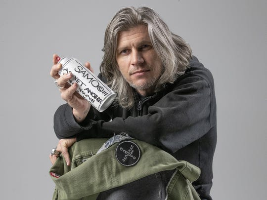 Visual artist Matthew Aaron holds a spray paint can customized by Al Diaz, the New York City street artist who co-founded the SAMO© graffiti team with Jean-Michel Basquiat in 1978. Aaron and Diaz will show their collaborations in an upcoming exhibition at Carmel's Evan Lurie Gallery.