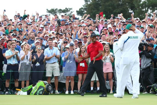 Apr 14, 2019; Augusta, GA, USA; Fans cheer as Tiger Woods leaves the 18th green after winning The Masters golf tournament at Augusta National Golf Club.