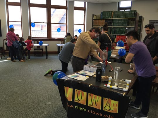Scientists at the University of Iowa Sciences Library engaging in hands-on experiments with the public on April 20, 2018.