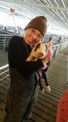 Brenda Graham holds a hog in the animal confinement operated by her family in Poweshiek County