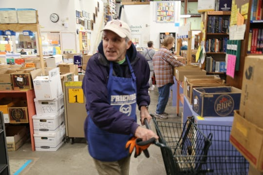 Rick Hautala, of Danby, pulls a cart at the Friends of the Tompkins County Public Library warehouse.