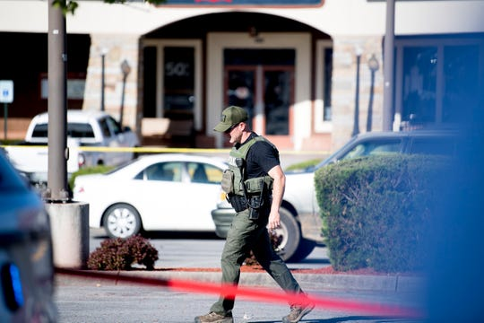 A police officer walks at the scene of a shooting outside of Coach at the Tanger Outlet Mall in Sevierville, Tennessee on Tuesday, April 16, 2019. Two people including the assailant, were found dead at the scene with a third suffering from a gunshot wound.