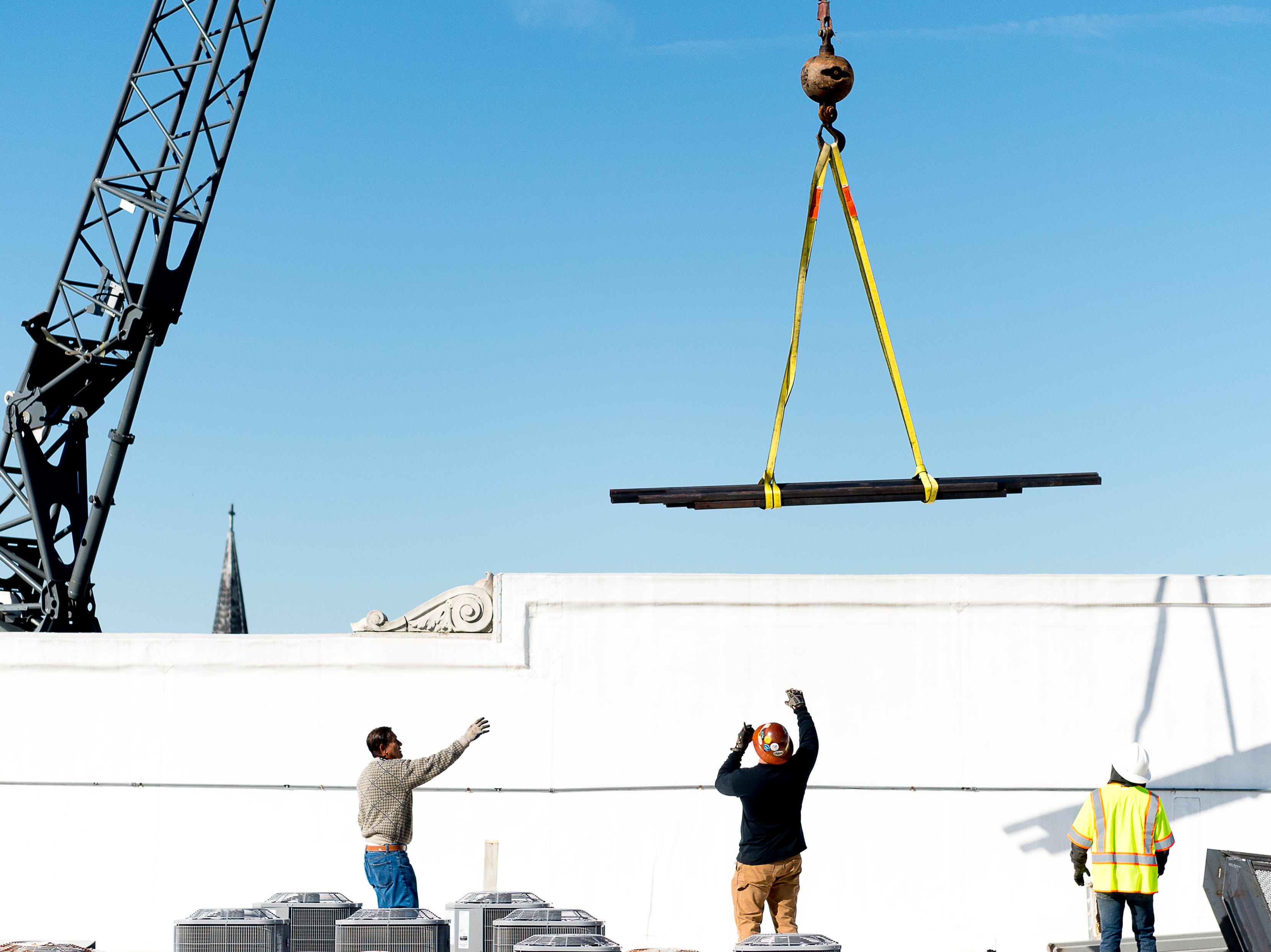 Crews set down equipment on the roof of Sterchi Lofts after being hoisted up by a crane in Knoxville, Tennessee on Tuesday, April 16, 2019. A new railing costing an estimated $70,000 is being installed to reopen the rooftop patio this summer.