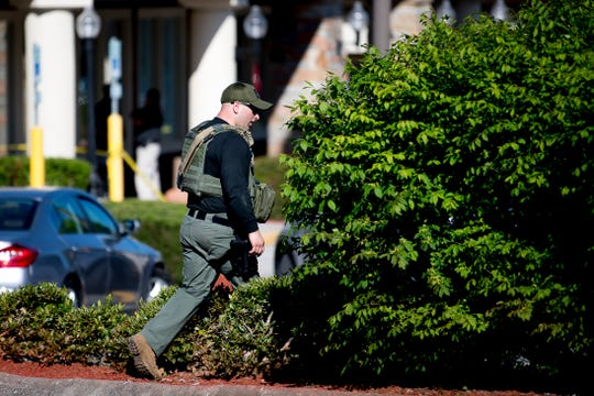 A police officat the scene of a shooting outside of Coach at the Tanger Outlet Mall in Sevierville, Tennessee on Tuesday, April 16, 2019. Two people including the assailant, were found dead at the scene with a third suffering from a gunshot wound.