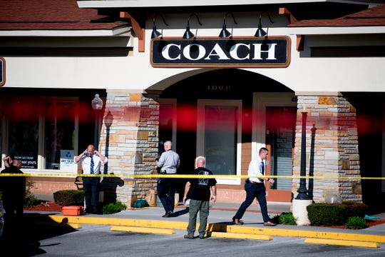 Investigators walk at the scene of a shooting outside of Coach at the Tanger Outlet Mall in Sevierville, Tennessee on Tuesday, April 16, 2019. Two people including the assailant, were found dead at the scene with a third suffering from a gunshot wound.