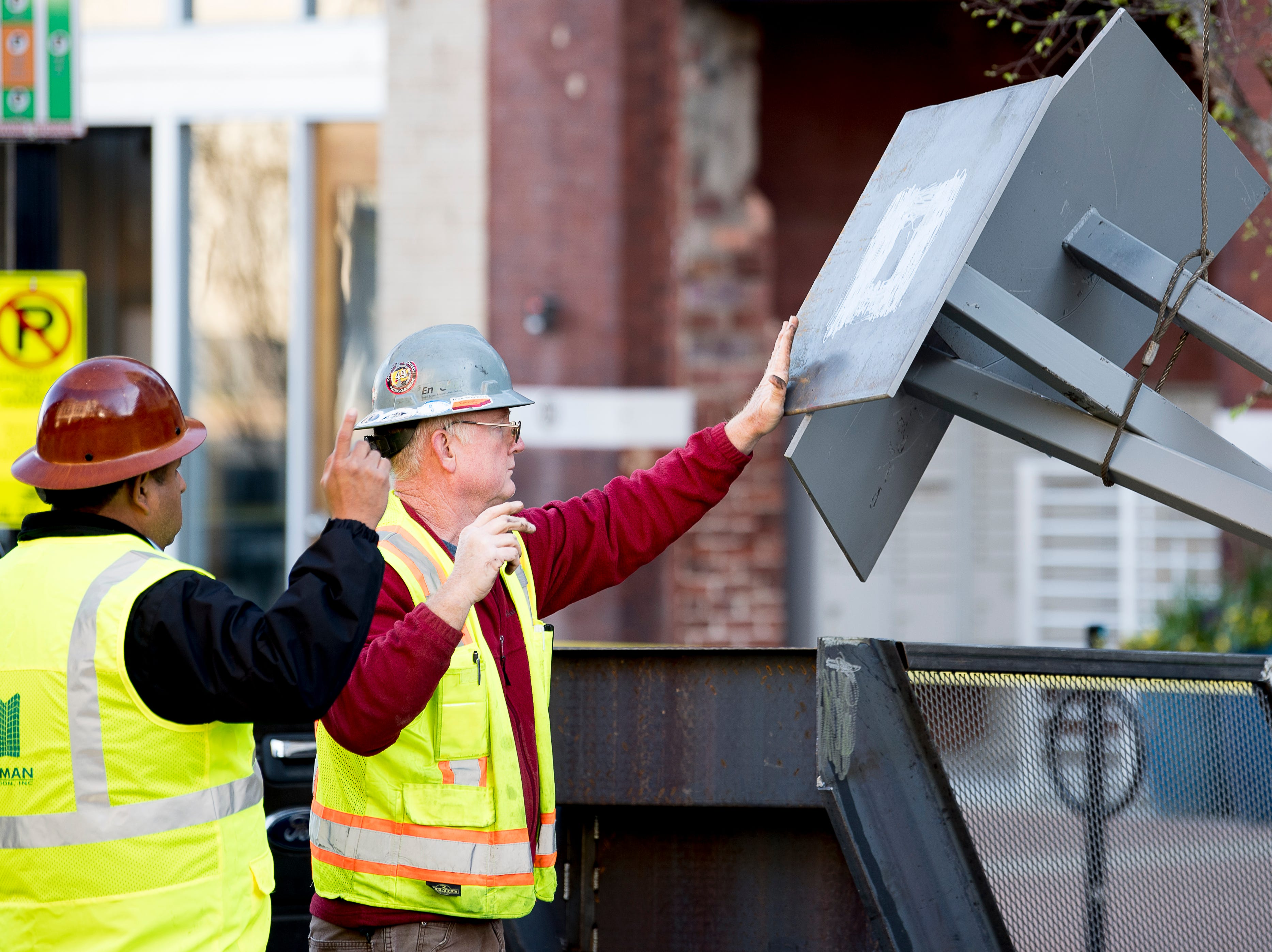 Crews fasten equipment to a crane to hoist to the roof of Sterchi Lofts in Knoxville, Tennessee on Tuesday, April 16, 2019. A new railing costing an estimated $70,000 is being installed to reopen the rooftop patio this summer.