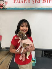 Broadmoor Elementary student Clara holds certified therapy dog Palan during a Moana-themed third birthday party for the dog during A.P.E. class. Clara was scared of dogs before teacher Courtney Vincent introduced Palan into class. Now Clara has a dog at home.