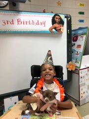 Broadmoor Elementary student Kayden holds certified therapy dog Palan during a Moana-themed third birthday party for the dog during A.P.E. class. Courtney Vincent introduced Palan into class.