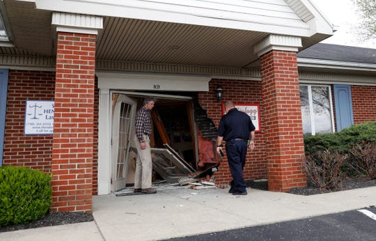 Kevin Schmelzer, left, who handles maintenance for the building at 1303 River Valley Boulevard and Lancaster Fire Capt. Brian Archer look at the damage done to the building after an elderly woman drove a car into it. Lancaster Police said the woman reversed her Honda Civic after hitting the building and crossed two grass medians, four lanes of traffic on River Valley Boulevard, drove over a row of bushes and through the Target parking lot and hit the store. The damage to Target was minimal.