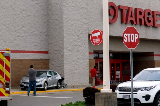 Target employees set up barriers around a crashed Honda Civic Tuesday, April 16, 2019, in Lancaster. According to Lancaster Police, the 89-year-old female driver reversed her Honda Civic after hitting the building at 1303 River Valley Boulevard and crossed two grass medians, four lanes of traffic on River Valley Boulevard, drove over a row of bushes and through the Target parking lot and hit the store. The damage to Target was minimal. The entrance to the 1303 River Valley Boulevard was destroyed in the crash.