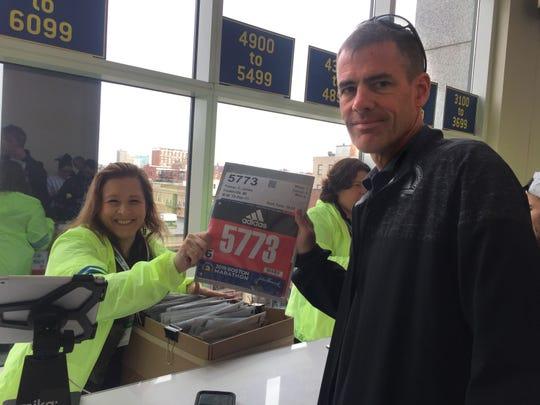 Jim Palmer of Fowlerville picks up his bib number before the 123rd Boston Marathon.