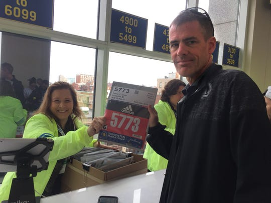 Jim Palmer of Fowlerville picks up his bib number before the 123rd Boston Marathon.