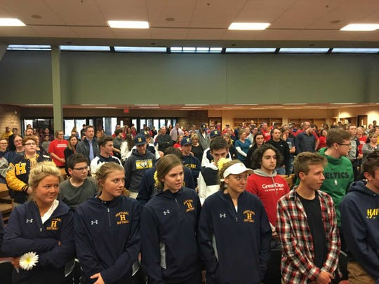 Several dozen people, including teachers, students and former students, stood up in support of Brian Morrison, a teacher and coach at Hartland Consolidated Schools, during a Board of Education meeting Monday April 15, 2019. Morrison was placed on paid leave after an incident with a student.