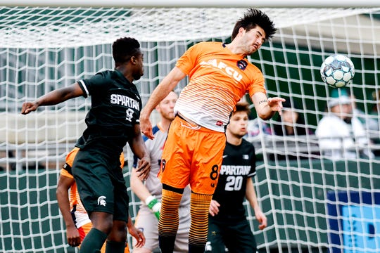 Lansing Ignite's Kyle Carr, right, heads the ball away from the goal after a Michigan State corner kick during the first half on Tuesday, April 16, 2019, at Cooley Law School Stadium in Lansing. Michigan State's Farai Mutatu, left, looks on. The Lansing Ignite played the Michigan State Spartans for the inaugural Capital Cup.