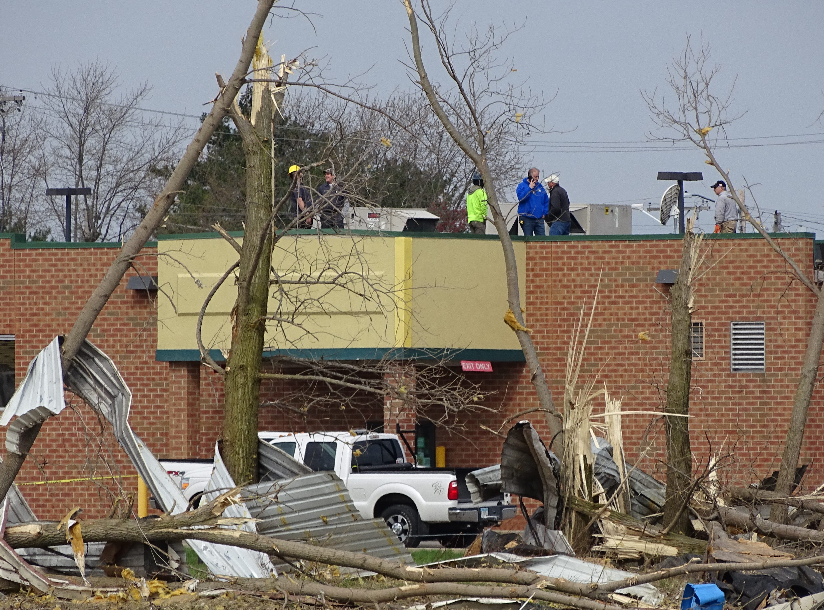 Workers stand on the roof of Discount Drug Mart on Ohio 39 in Shelby, which remained closed Tuesday. The building was damaged when an EF-2 tornado hit the community on Sunday.