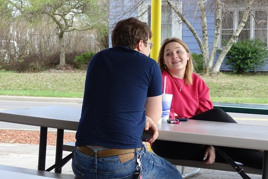 Sydney Harris, 16, chats with Elijah Harris, 18, outside the Dairy Crest on East Mansfield Street on Tuesday afternoon. The local eatery opened for the season on Monday.