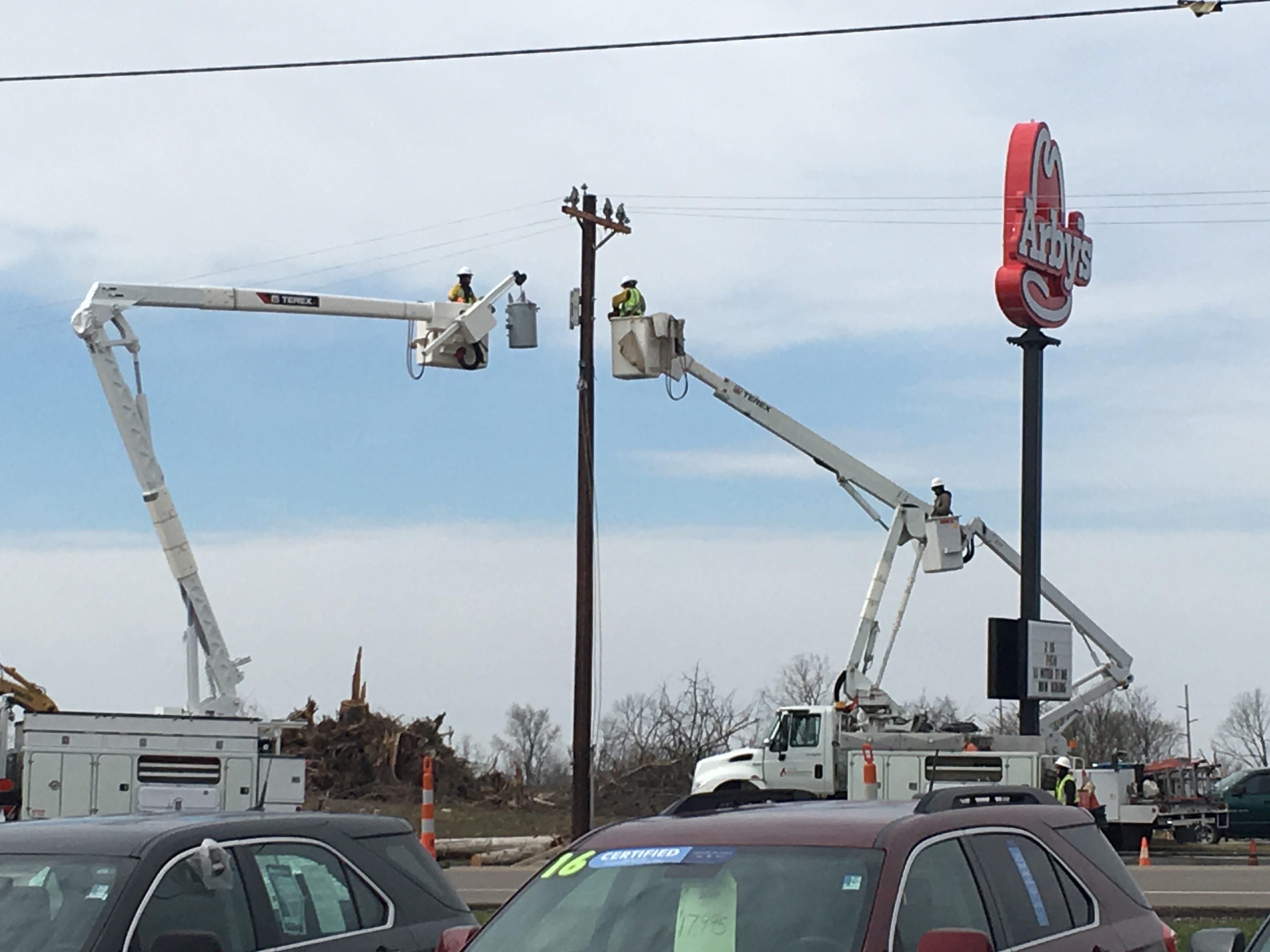 Crews were busy Tuesday repairing utility lines damaged by Sunday's twister.