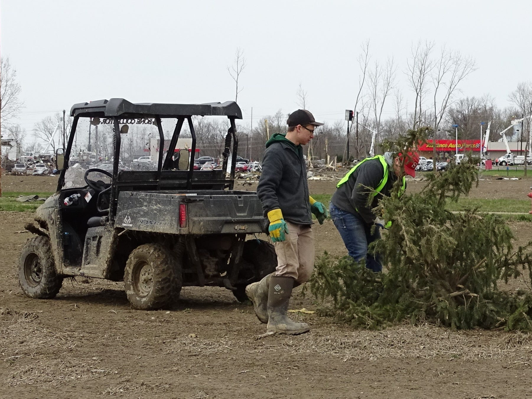 Shelby FFA President Owen Wallace, front, works with a fellow member to clear a field along Technology Parkway on Tuesday. The FFA members volunteered to help with cleanup after Sunday's tornado.