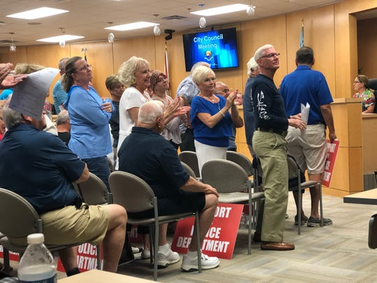 A packed crowd at the Marco Island City Council meeting claps for Police Chief Al Schettino.
