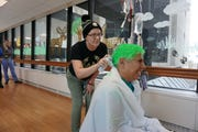 Patient Kenda Koepp, 20, uses green spray on Dr. David Margolis as he flinches at Children's Hospital of Wisconsin. The green hair is to show support for the Milwaukee Bucks' march to the NBA championship and patients such as Koepp.
